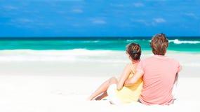 在海滩和有乐趣的年轻家庭sittin 免版税库存图片