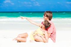 在海滩和有乐趣的年轻家庭sittin 库存照片