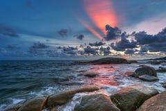 在海滨和美丽的暮色天空的岩石 库存图片