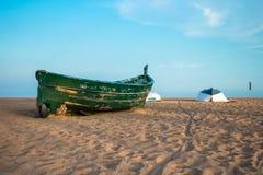 在海滩和蓝天的绿色渔船 库存照片