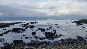 在海洋和被覆盖的天空的岩石 库存照片
