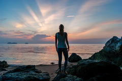 在海滩和观看日落的女孩逗留 免版税库存图片