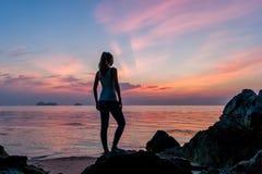 在海滩和观看日落的女孩逗留 免版税库存照片