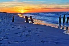 在海滩和防堤的日落 免版税库存图片