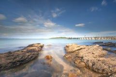 在海滩和biue天空的岩石 免版税库存图片
