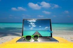 在海滩-商务旅游背景的计算机笔记本 免版税图库摄影