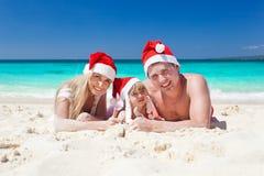 在海滩在圣诞老人帽子,庆祝圣诞节的愉快的家庭 免版税库存图片