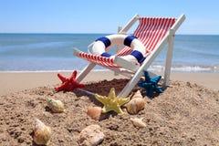 在海洋壳附近的海滩睡椅 免版税库存照片