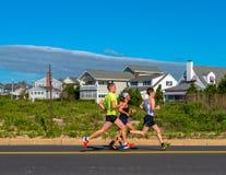 在海洋大道的三个赛跑者 免版税库存照片