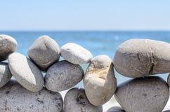 在海洋天际前面的岩石墙壁 免版税库存图片