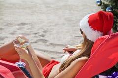 在海滩女孩的圣诞节圣诞老人帽子的 免版税图库摄影