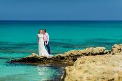 在海洋岸的一对婚礼夫妇 免版税库存图片