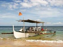 在海滩岸的木舷外架小船 库存图片