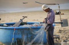 在海滩工作的渔夫 免版税库存照片