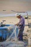 在海滩工作的渔夫 免版税图库摄影