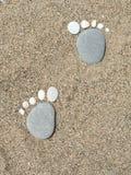 在海滩-巨足兽的逗人喜爱的石脚印 图库摄影