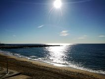 在海滩离开的地中海海岸的晚黎明 免版税库存图片