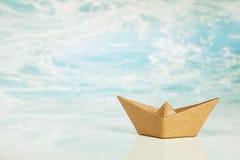 在海洋或水背景隔绝的一条包装纸小船为 库存图片