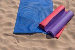 在海滩投掷的瑜伽席子-为教训做准备 库存照片