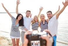 在海滩挥动的手和拍摄上的朋友 免版税库存图片