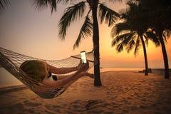 在海滩摇篮和拍摄照片的妇女由聪明的pho 免版税库存照片