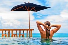 在海滩无限水池的女子游泳有海视图 库存照片