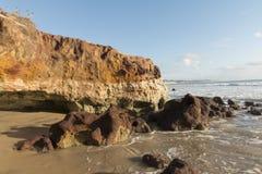 在海滩-日出的五颜六色的峭壁 免版税库存图片