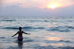 在海滩日落的妇女戏剧 免版税库存图片