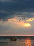在海滩日落的空的小船 免版税库存照片