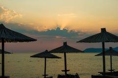 在海滩日落的遮阳伞 免版税库存照片