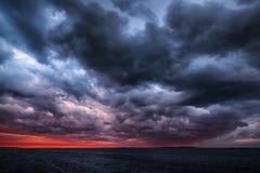 在海洋日落的风暴 免版税库存照片