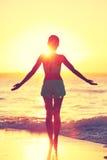 在海滩早晨日出的留心女子实践的瑜伽太阳致敬 免版税图库摄影