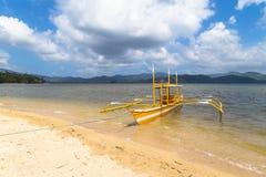在海滩有一条黄色小船,在海岛的背景中 库存照片