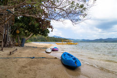在海滩有一条黄色小船,在海岛的背景中 图库摄影
