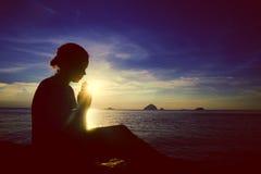 在海洋概念的少妇祈祷的日落 免版税库存照片