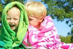 在海滩毛巾包裹的兄弟嘻嘻笑 图库摄影