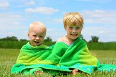 在海滩毛巾包裹的兄弟 免版税库存照片