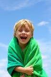 在海滩毛巾包裹的笑的孩子 库存图片