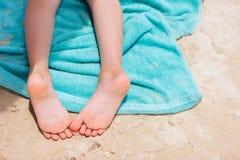 在海滩毛巾的小女孩脚 图库摄影