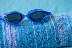 在海滩毛巾的蓝色游泳风镜 免版税库存图片