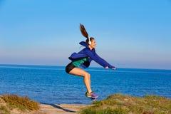 在海滩沙丘的赛跑者女孩跳跃的锻炼 库存照片