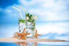 在海滩沙子和热带海景的Mojito鸡尾酒 库存图片