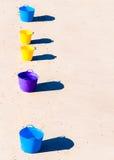 在海滩沙子的五颜六色的桶 库存图片