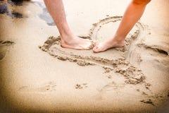 在海滩沙子的夫妇的腿 图库摄影