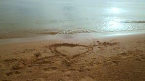 在海滩沙子的心脏形状 平稳的射击 在沙子海滩的心脏凹道 股票视频