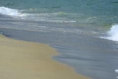 在海滩沙子的波浪 库存照片