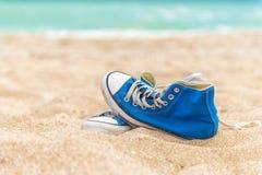 在海滩沙子的蓝色被佩带的运动鞋 免版税库存图片