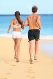 在海滩沙子的跑步的连续年轻健身夫妇 库存照片
