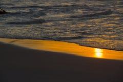 在海滩沙子的金黄反射在波浪崩溃以后 库存图片