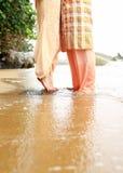 在海滩沙子的年轻夫妇腿 图库摄影